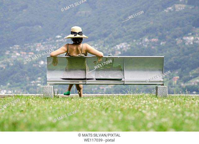 Woman with a straw hat in summer sitting on a bench