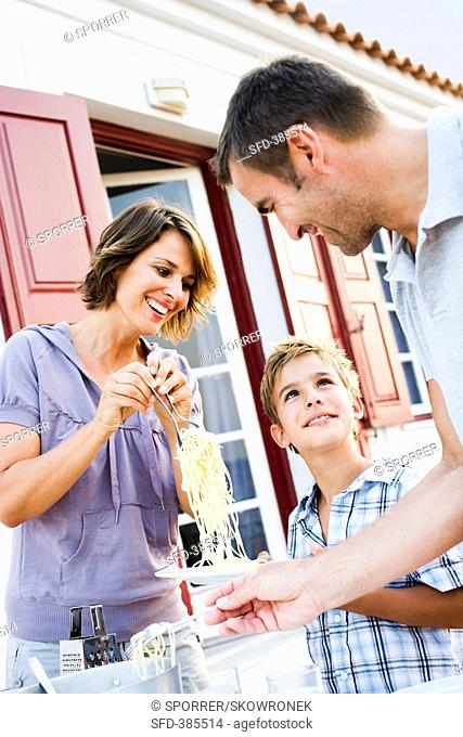 Family with son eating spaghetti out of doors