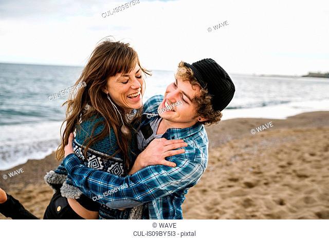 Young man lifting girlfriend on beach, Barcelona, Spain