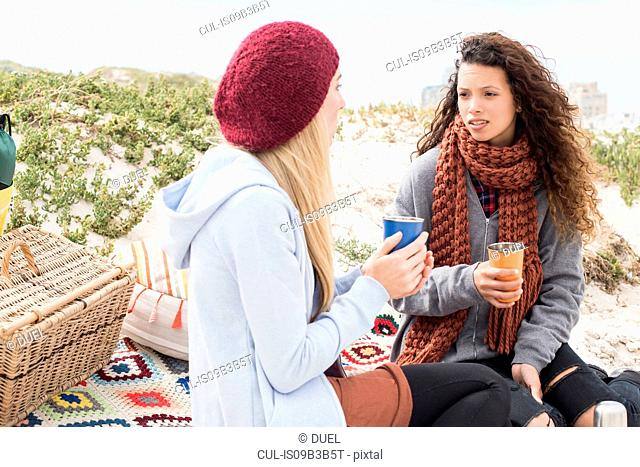 Two young women chatting beach picnic, Western Cape, South Africa