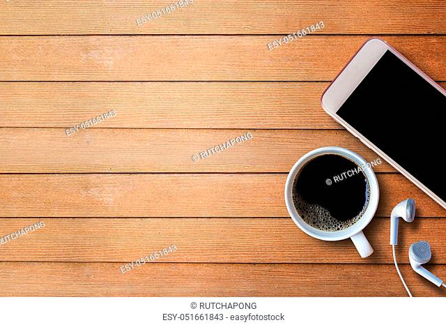 Cup of coffee with smart phone and earphone on wood table background with copy space for any design. smart phone and coffee cup on wooden top view