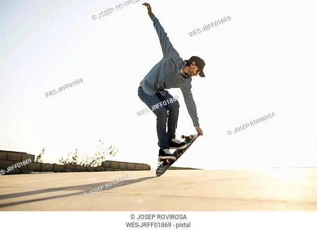 Trendy man in denim and cap skateboarding, standing on skateboard