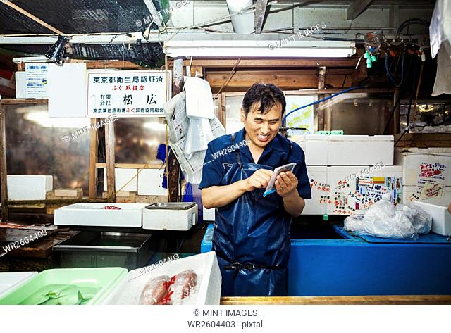 A traditional fresh fish market in Tokyo. A man in a blue apron standing behind the counter of his stall, using a smart phone covered with protective plastic