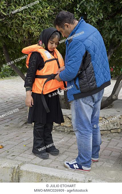Father refugee from Afghanistan try a life vest on her daughter in a park in Cesme, Izmir, Turkey. They are waiting to be taken by smugglers to Greece
