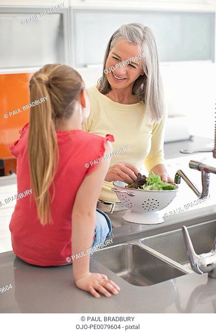 Granddaughter watching grandmother rinsing lettuce