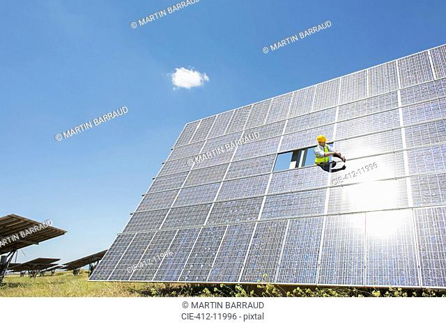 Worker examining solar panel in rural landscape