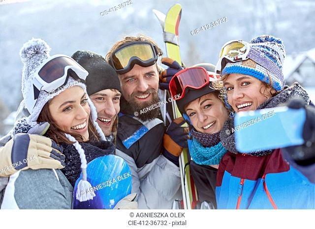 Smiling skier friends taking selfie with camera phone