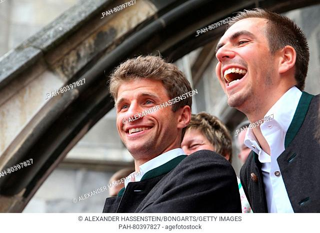 MUNICH, GERMANY - MAY 15: Thomas Mueller of Bayern Muenchen and his team mate Philipp Lahm (R) celebrates winning the German Championship title on the town hall...