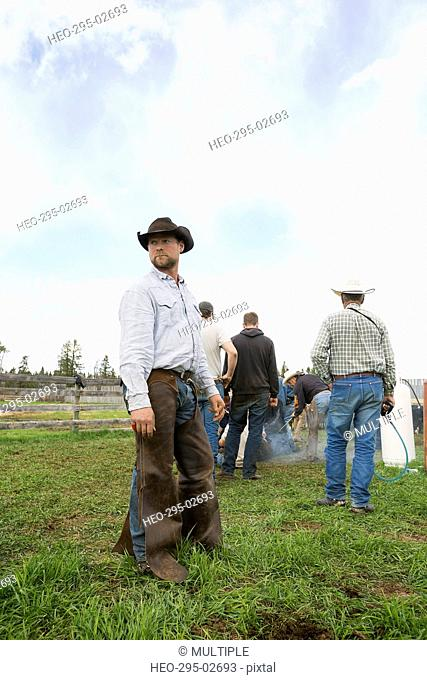 Cattle rancher in cowboy hat and chaps looking away