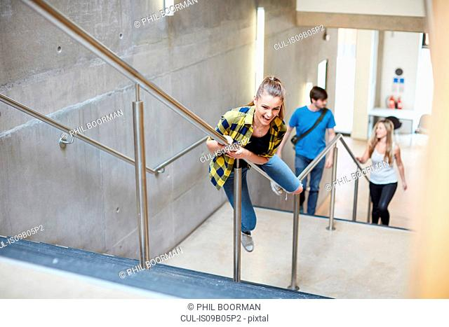Young female student sliding down stairway handrail at higher education college