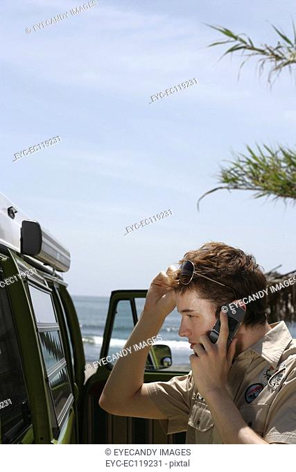 Young man on cell phone at beach