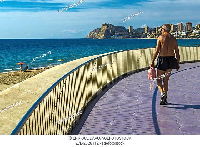 A bather walking near of Benidorm beach, Alicante province, Spain