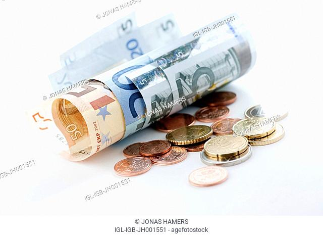 A roll of various euro banknotes and euro coins