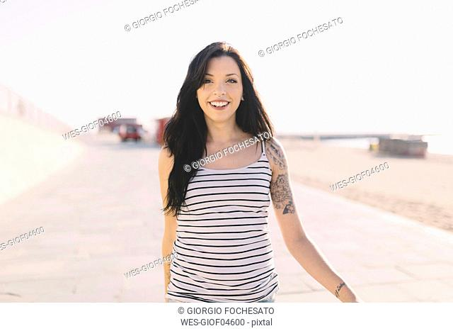 Portrait of smiling young woman with tattoo walking on beach promenade