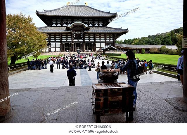 A visitor standing next to a koro (incense burner) lighting and incense stick at one of Japan's most historically significant temples The temple is a listed...