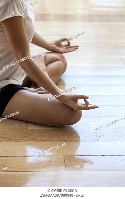 Woman meditating in lotus position, cropped