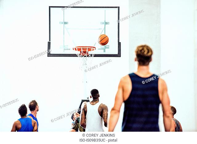Rear view of male basketball team watching ball going into hoop on basketball court