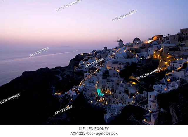 An aerial view of Oia and the windmill at dusk; Oia, Santorini, The Cyclades, The Aegean, The Greek Islands, Greece