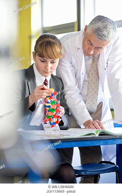 Science teacher helping high school student assembling helix DNA model