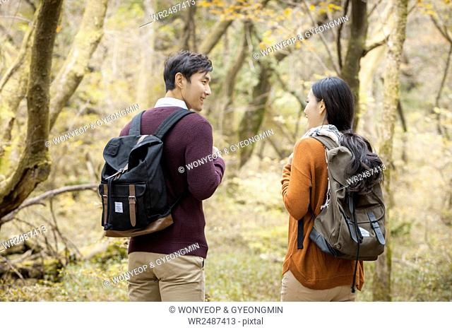 Back of young smiling couple trekkers face to face in forest in fall