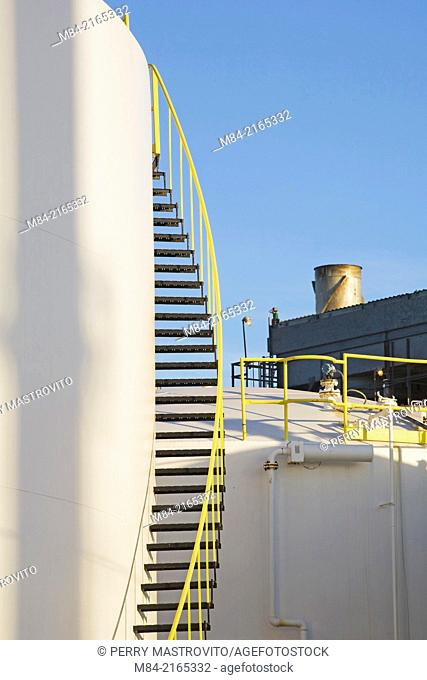 White oil storage tank with black and yellow metal staircase at an oil and gas refinery, Montreal, Quebec, Canada