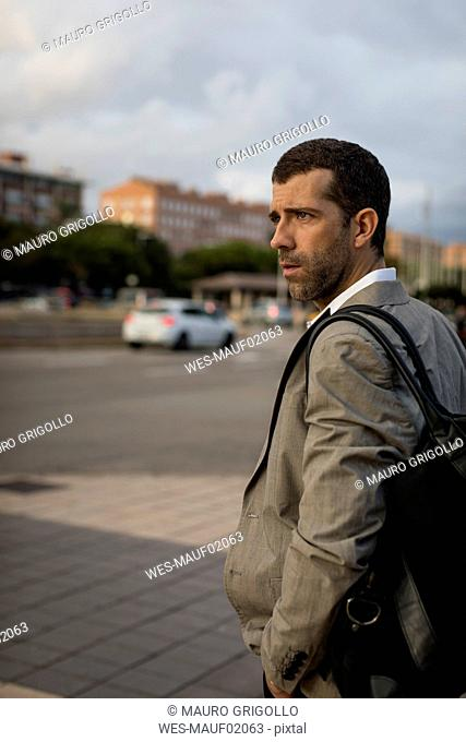 Businessman with bag standing in the city looking around