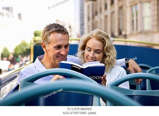 A middle-aged couple sitting on a sightseeing bus, looking at a guidebook