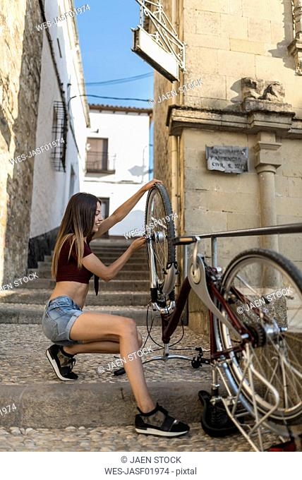 Spain, Baeza, smiling young woman adjusting her bicycle