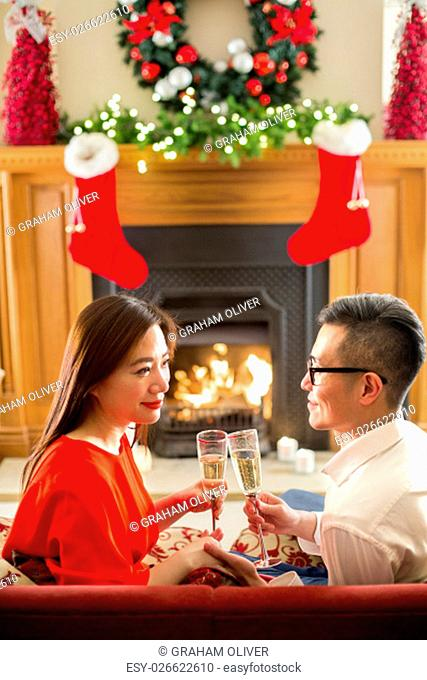 Chinese couple enjoying a glass of bubbly on christmas evening. they are sitting in front of the fire, holding hands and smiling lovingly at each other