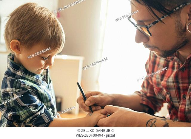 Father painting tattoo on son's hand