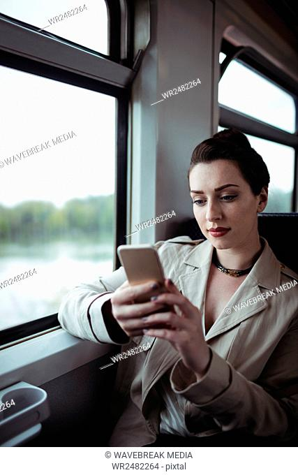 Woman using cellphone in train