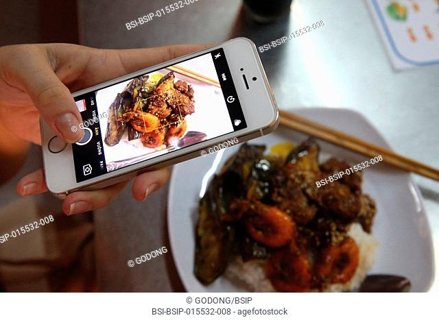 Woman using her smartphone to take a picture of her meal. Hoi An. Vietnam
