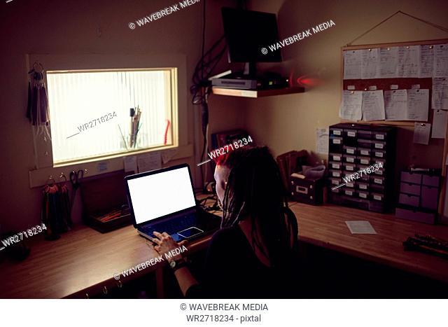Female hairdresser using laptop