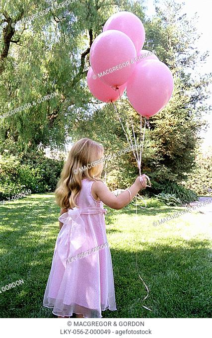 Young girl waits for birthday party guests with balloons in her hand