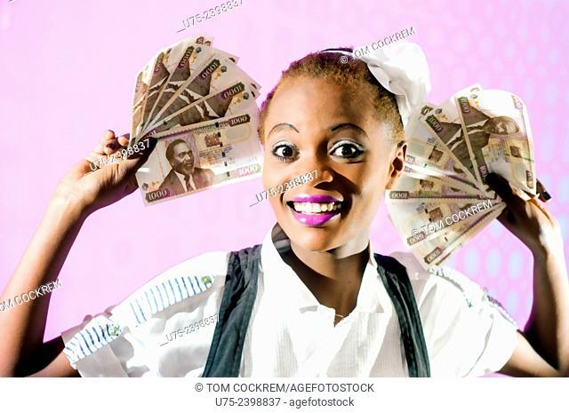 Kenyan woman with Kenyan 100 shilling notes in studio setting
