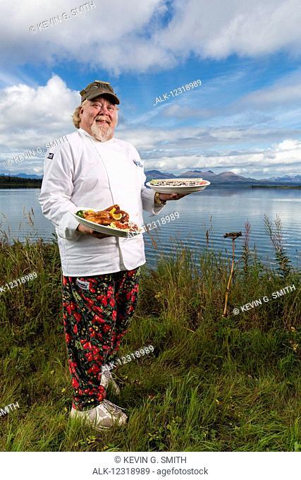 Tikchik Narrows Lodge Chef, Matt Spence, holding his Peking Duck and Sushi rolls on the shore of Tikchik Lake, Wood-Tikchik State Park, Southwest Alaska, USA