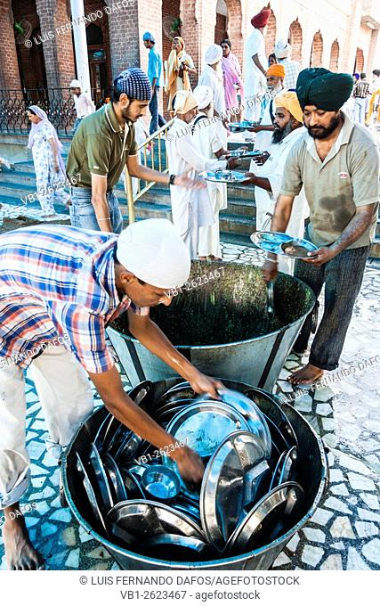 Sikh volunteers washing dishes at the Golden Temple in Amritsar, India