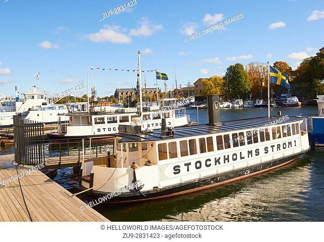 Boats flying Swedish flag moored on waterfront, Stockholm, Sweden, Scandinavia