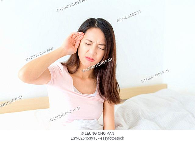 Woman with headache sitting on her bed
