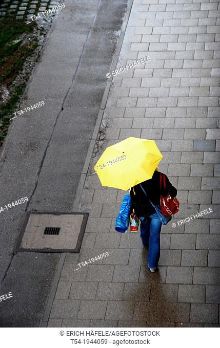Woman goes with yellow umbrella