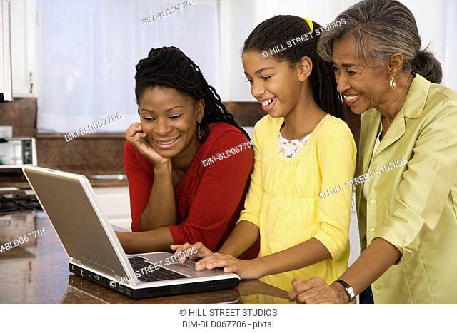 African girl showing mother and grandmother how to use laptop