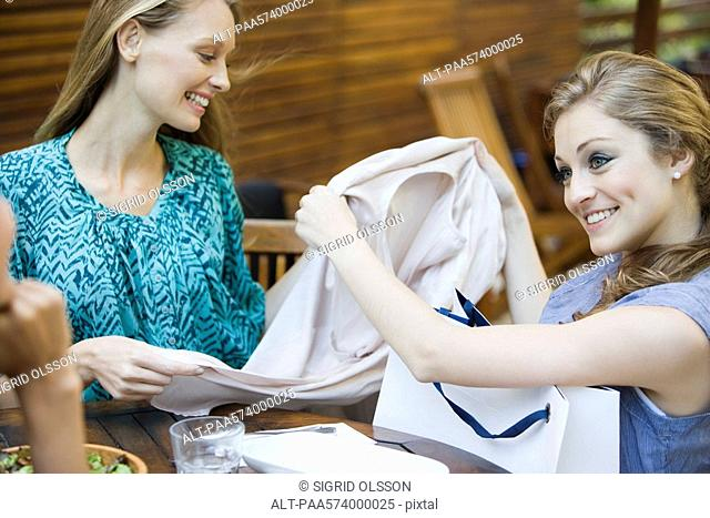 Friends together in outdoor cafe, one woman showing new clothing in shopping bag