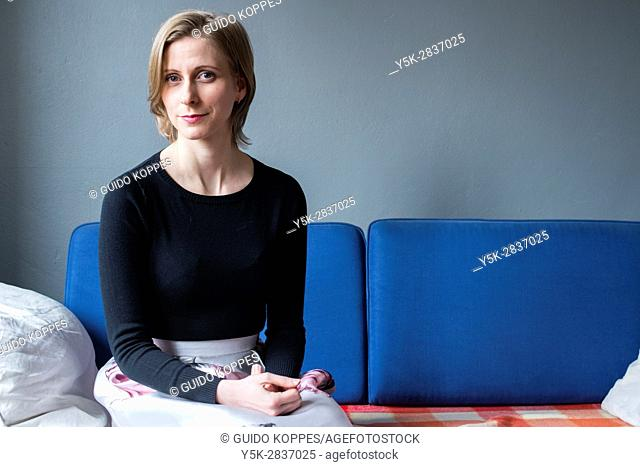 Tilburg, Netherlands. Attractive caucasian woman neatly sitting on a living room couch, wearing a clolorfull skirt
