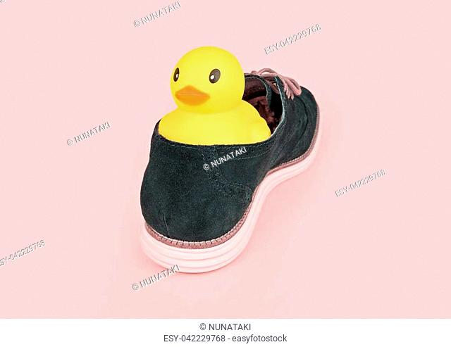 Large yellow rubber duck in blue male boot on pink background. Inundated concept