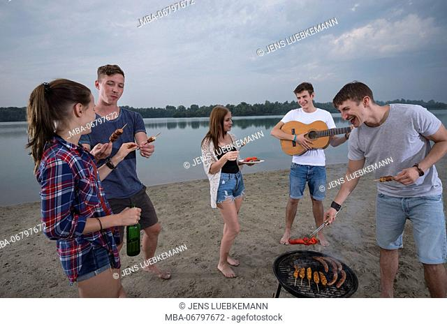 Youths at grill party on the beach, quarry pond Liedolsheim, Dettenheim, Baden-Wurttemberg, Germany