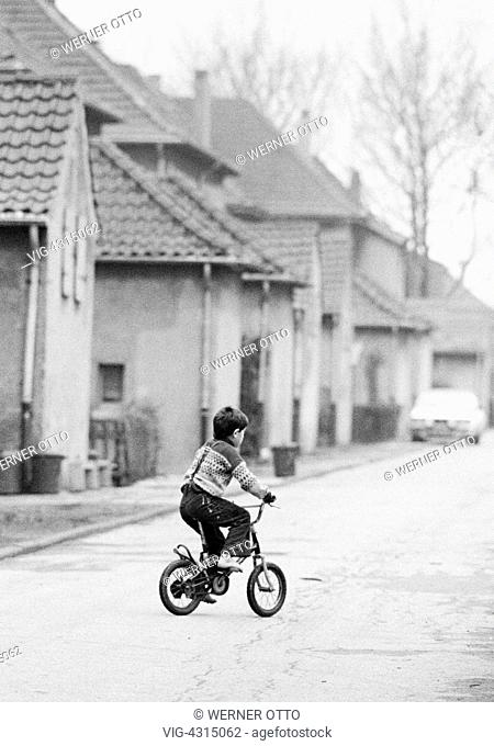 DEUTSCHLAND, OBERHAUSEN, 15.12.1980, Eighties, black and white photo, people, children, little boy drives on a childrens bicycle across a traffic street
