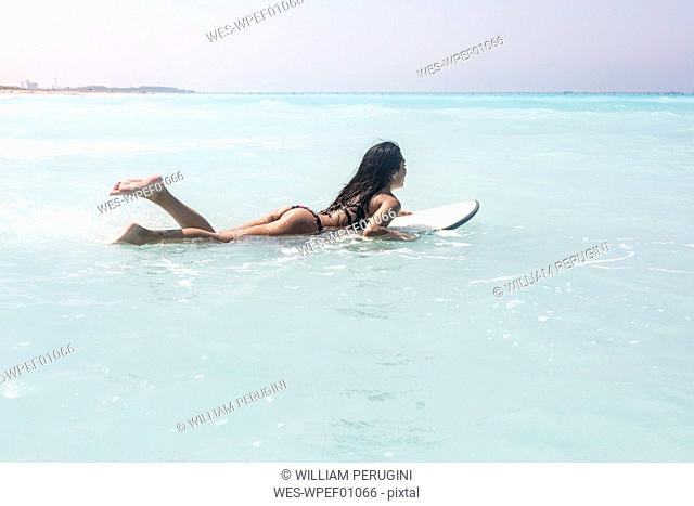 Young woman lying on surfboard, floating on the sea