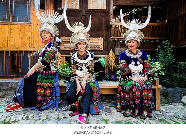 China, Guizhou, three Miao women wearing traditional dresses and headdresses