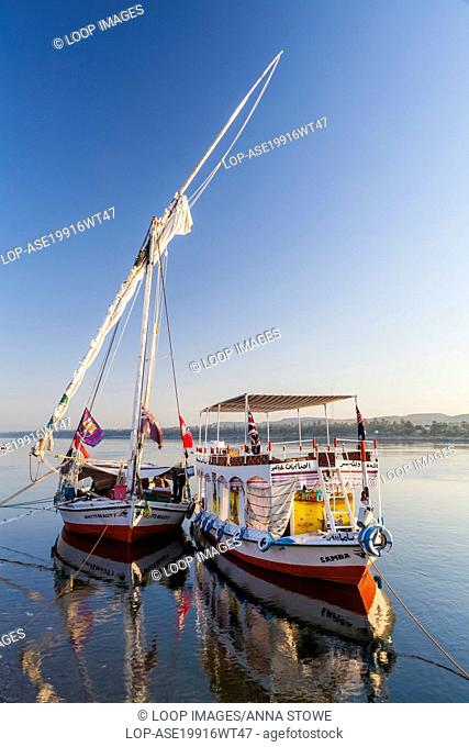 Tourist felucca and support boat moored along the bank of the Nile near Aswan at sunrise