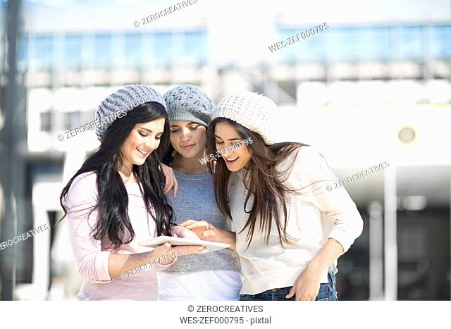 Three female friends with wool caps using digital tablet
